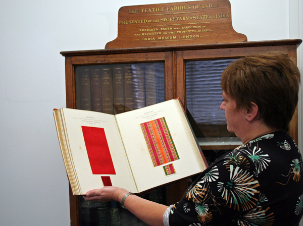 Clare Lamkin with one of the Textile Fabrics of India volumes and the original presentation cabinet