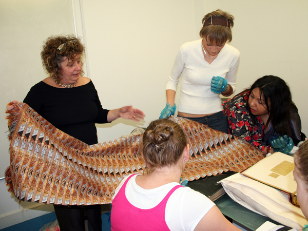 Ruth Caswell shows the woven cloth to the students